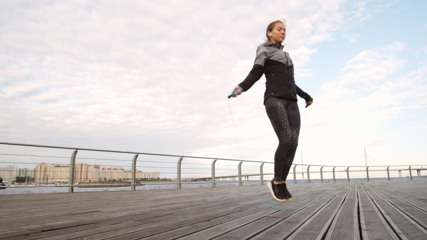 Wide shot of young sporty Caucasian woman jumping using jump rope on wooden embankment outdoors while listening to music using wireless headphones #1035076592