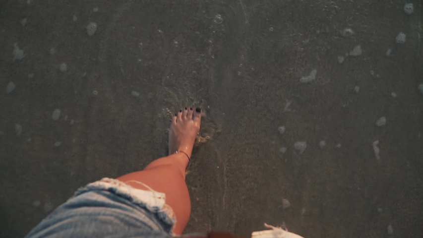 Top view close-up of young woman legs standing on sea shore at sunset. Foamy sea waves gently wash sand and feet, warm soft evening sun reflects on wet surface. First person view slow motion footage. | Shutterstock HD Video #1035083612