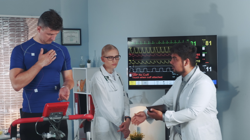 Multriracial cardiologist checking data signals sending by each electrode on athlete and comparing with the data on the screen. In Scientific Sports Laboratory. | Shutterstock HD Video #1035098852