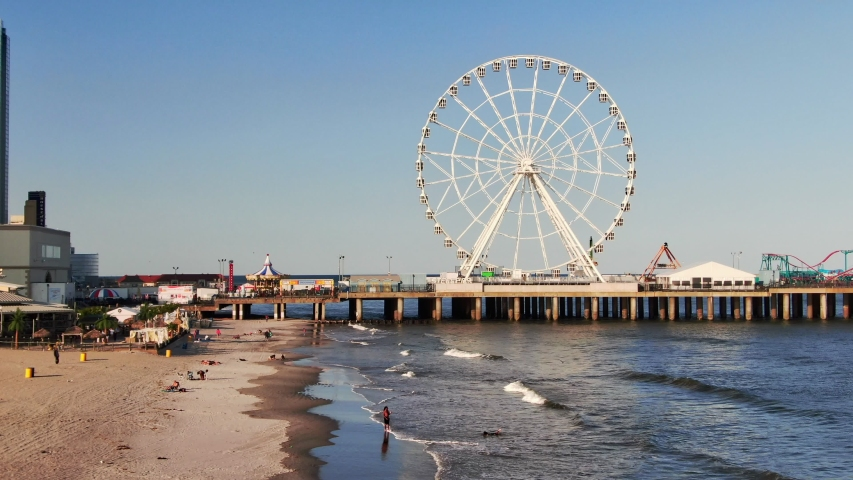Atlantic City , New Jersey / United States - 06 03 2019: Atlantic City, New Jersey with Ferris Wheel, beachfront and the boardwalk with casinos and hotels on the beachfront, aerial view