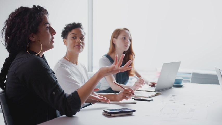 Team Of Young Businesswomen With Laptops And Tablets Meeting Around Table In Modern Workspace | Shutterstock HD Video #1035131342