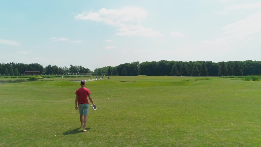 Aerial view of man with virtual reality headset in his hands, who walks along the green grass among beautiful trees and forest, blue sky with clouds on sunny day in the summer time. 4K drone footage.   Shutterstock HD Video #1035175862