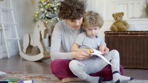 Lovely little boy sitting together with mom and cutting out paper decorations for holiday in cozy kids room with Christmas tree