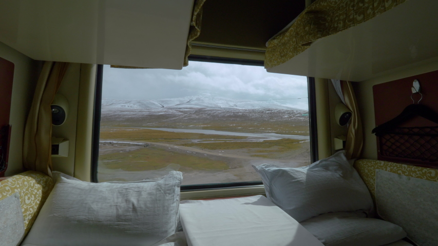 CLOSE UP: Sleeper train window provides a stunning vista of the rugged Himalayan nature. Two comfortable beds remain empty in a private sleeping cabin of an overnight train crossing picturesque Tibet. | Shutterstock HD Video #1035233492