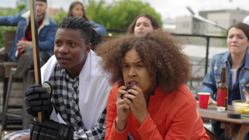 Young African man and woman sitting with hockey puck and stick and yelling in excitement while watching match with multiethnic friends in outdoor bar on urban rooftop | Shutterstock HD Video #1035272522