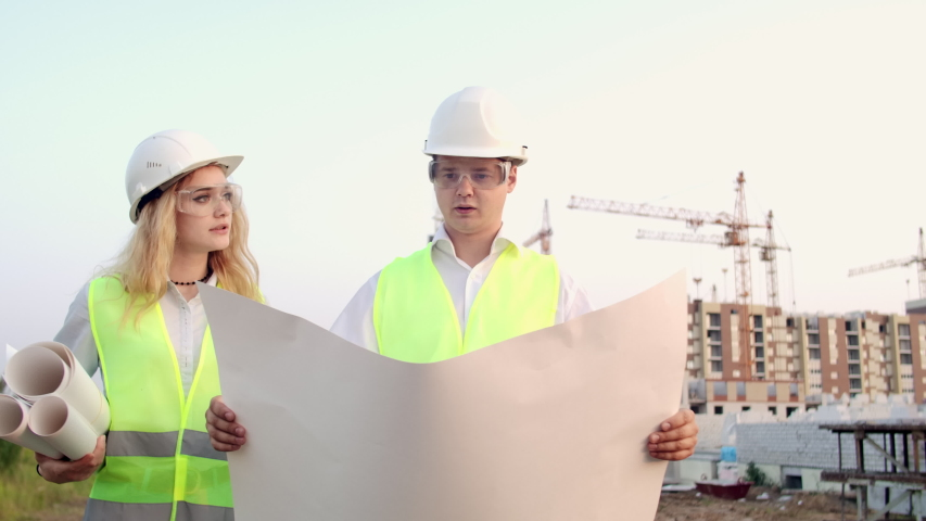Engineer and supervisor go to the construction site to look at the drawings on the background of cranes and talk about work. Discussion with the contractor on the construction progress | Shutterstock HD Video #1035355322