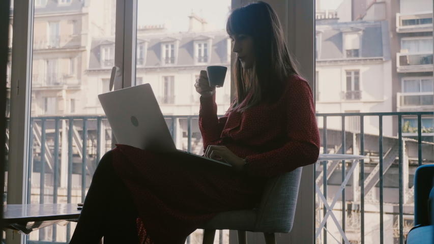 Happy successful beautiful Caucasian businesswoman using laptop smiling at beautiful Paris hotel window on vacation. | Shutterstock HD Video #1035394232