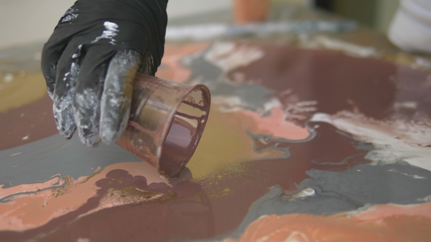 Workshop of liquid acrylics. Fluid art. female hands pouring acrylic paint on canvas. Creative work | Shutterstock HD Video #1035400142