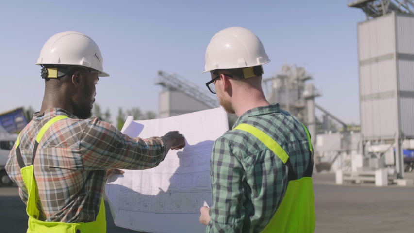 Back view of two construction engineers looking at blueprint standing at industrial site #1035420272