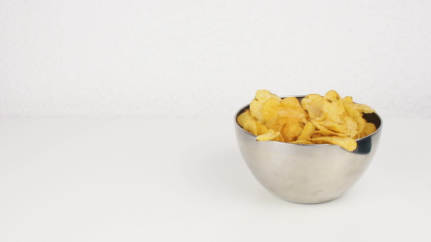 Female beautiful hands with take potato chips from a deep plate. Unhealthy food, fast food   Shutterstock HD Video #1035425372