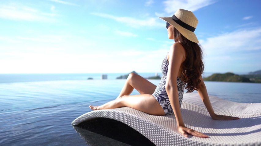 Woman lounging next next to a pool facing out toward the landscape in the distance. | Shutterstock HD Video #1035426152