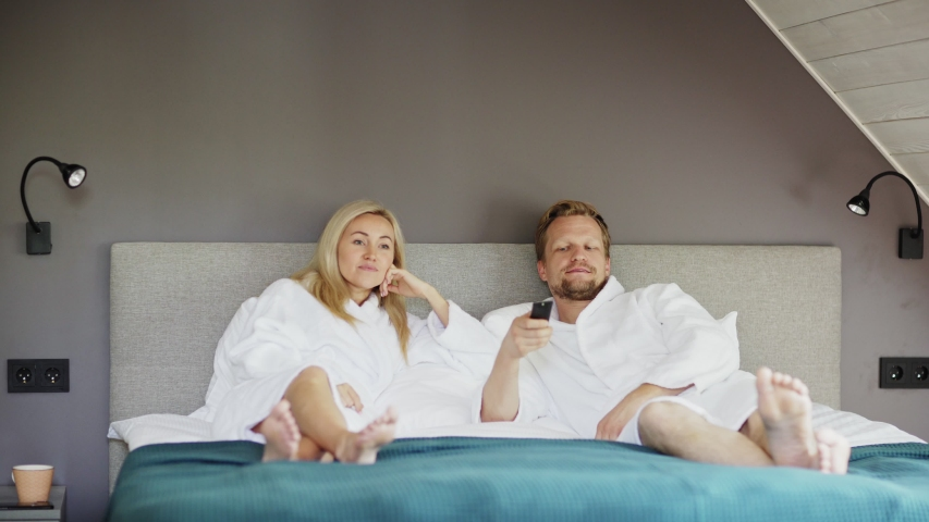 Married middle aged couple in white bathrobes lying on bed in hotel room and watching tv together. man switching channels with remote control | Shutterstock HD Video #1035426422
