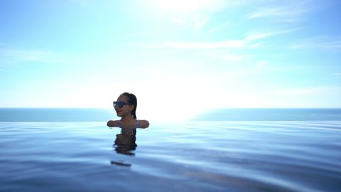 Woman in infinity pool with glasses with sunny background and copy space