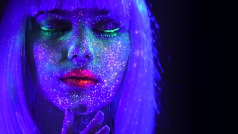 Fashion model woman in neon light, beautiful model girl colorful bright fluorescent make-up, painted skin, Body Art design of disco female in UV, colorful make up. Night club. 4K UHD video footage