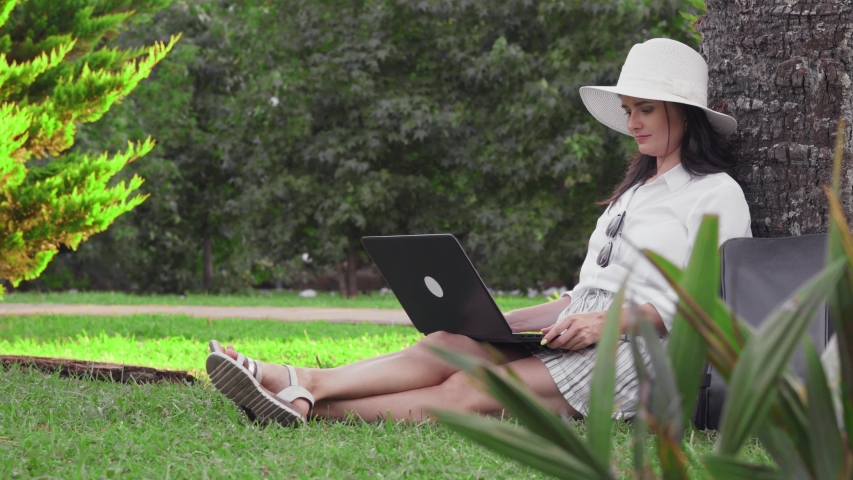 A brunette girl sits in a park on grass with a laptop, uses a phone. Sunny day in the park. The girl works in the park behind the laptop. | Shutterstock HD Video #1035438272