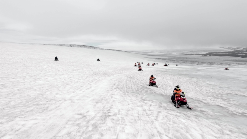 Aerial view of snowmobile tour driving in snowy hills.Arctic expedition atmosphere, north pole,winter landscape of Vatnajokull Glacier Iceland. Extreme sport,adventure and travel destination concept. | Shutterstock HD Video #1035489242