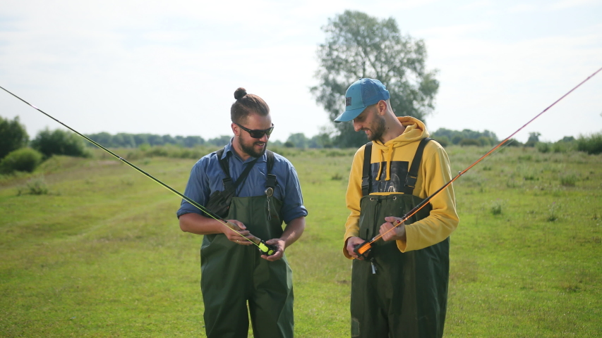 Two men fisherman, with black hair and beard, green overalls, holding a fishing rod and a float, communicate with each other, smile, on the street, by the river on the grass, Sunny weather, close-up | Shutterstock HD Video #1035537002