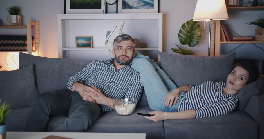 Girl and guy watching TV at night eating popcorn on couch together relaxing in dark room. Entertainment, relaxation and modern people concept. | Shutterstock HD Video #1035539042