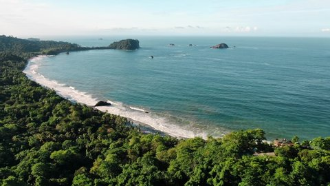 Drone Footage of Espadilla Beach near Manuel Antonio, Costa Rica on a Sunny Day with Small Beach Waves Crashing on the Shore and Cathedral Point in the Background