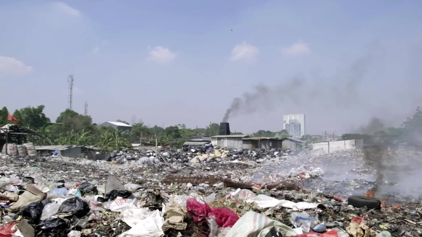 Landfill with a lot of trash and smoke near Jakarta area. There're a lot of pollution in this site. People burn everything and let it be inhaled by everyone. | Shutterstock HD Video #1035638972
