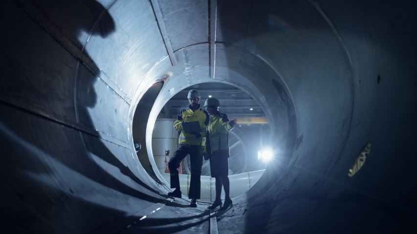 Two Heavy Industry Engineers Walking Inside Pipe, Use Laptop, Have Discussion, Checking Design. Construction of the Oil, Natural Gas and Biofuels Transport Pipeline. Industrial Manufacturing Factory | Shutterstock HD Video #1035704222