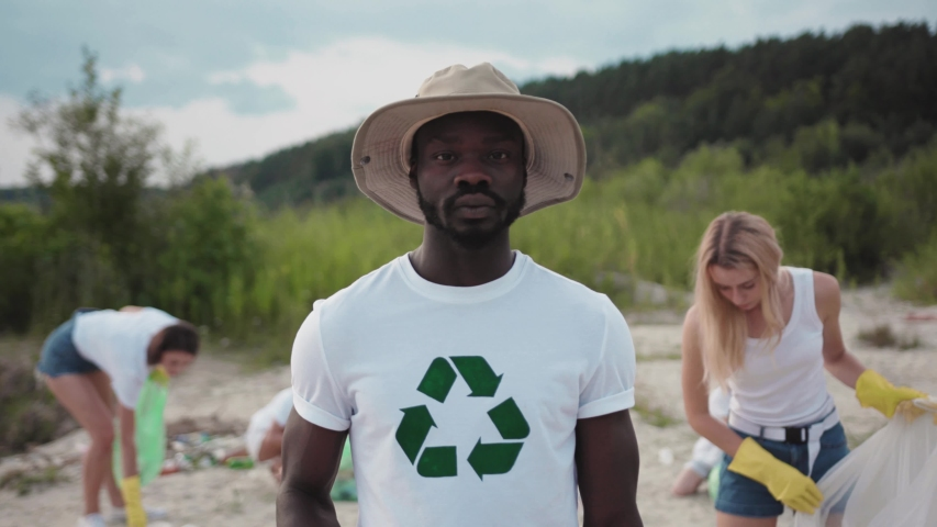 Portrait of afro-amercan ecology volunteer collecting garbage in plastic bags cleaning the beach up conducting a save environment program on the lake. Environmental moveme | Shutterstock HD Video #1035821522