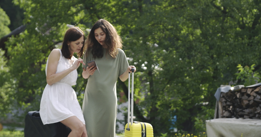 Two women with luggage using smarthone #1035901112