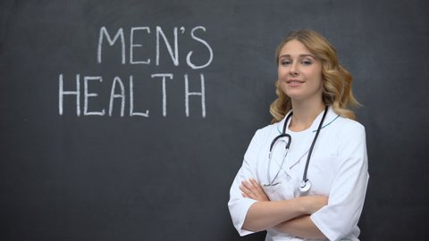 Doctor standing near Mens health inscription, importance of annual physical exam