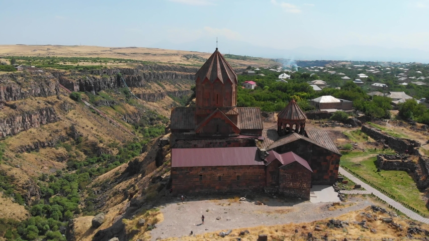 Hovhannavank medieval monastery located in the village of Ohanavan, Armenia. The monastery stands on the edge of the Kasagh River canyon.  Aerial flight view | Shutterstock HD Video #1035942332