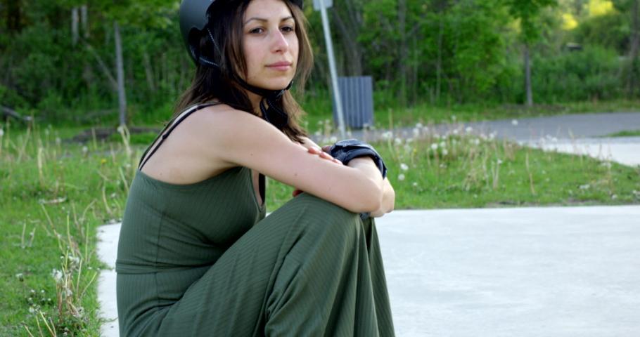 Female skateboarder sitting on skateboard at edge of skatepark - tilt down to board | Shutterstock HD Video #1036022942