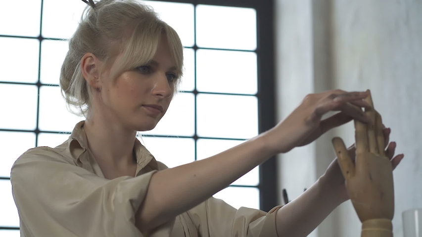 Female artist woman (designer) working with wooden hand. Slowmotion. | Shutterstock HD Video #1036131782