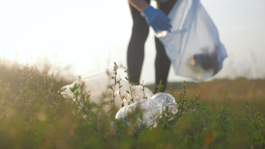 Care about nature. Volunteer girl collects trash in the trash bag. Trash-free planet concept. Nature cleaning, volunteer ecology green concept. Environment plastic pollution. | Shutterstock HD Video #1036162082