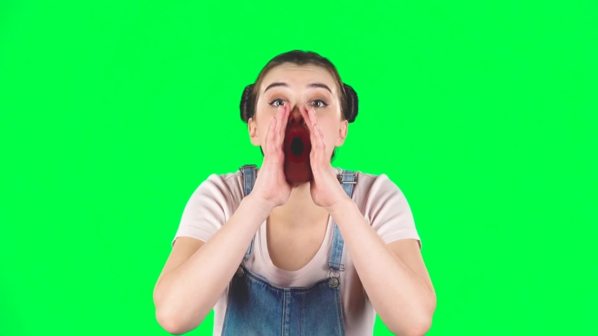 Girl screams calling someone on a green screen at studio. Girl with two hair-buns, wearing denim overalls and pink t-shirt. Concept of emotions, slow motion   Shutterstock HD Video #1036172132