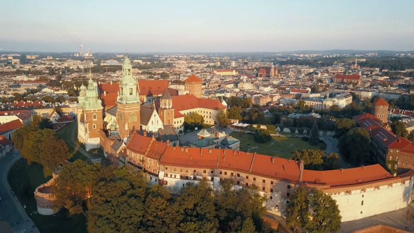 Aerial view of Royal Wawel Cathedral and castle in Krakow, Poland, with Vistula river, park, yard and tourists at sunset. Old city in the background | Shutterstock HD Video #1036208852