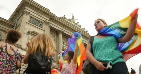 STRASBOURG - CIRCA 2015: Dancing waving gay flag in front of Strasbourg University at the 14th local edition of the Lesbian Gay Bisexual and Transgender LGBT visibility march, the Gay pride Festi Gays