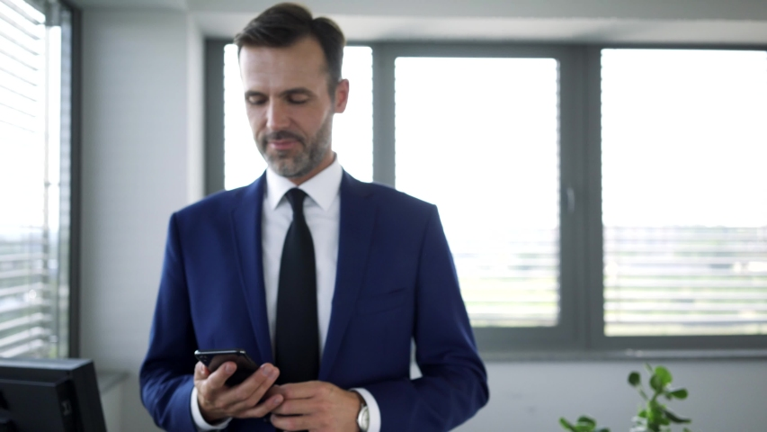 Cheerful businessman talking over phone and walking around office | Shutterstock HD Video #1036265882