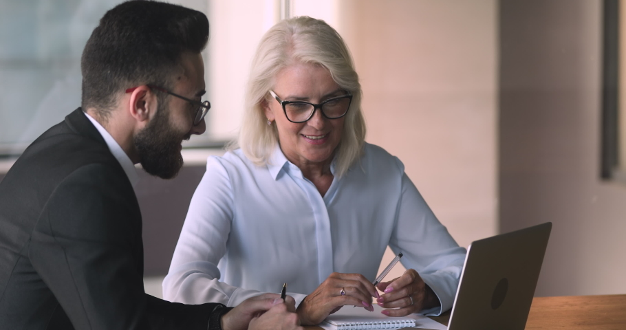 Old middle aged female professional bank manager investment advisor consulting commercial customer arabic eastern businessman explaining online project offer on laptop computer at business meeting   Shutterstock HD Video #1036280462