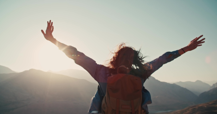Young girl standing on top of mountain and victoriously raising hands up, looking far away - zennism, freedom, adventure concept 4k footage #1036322582