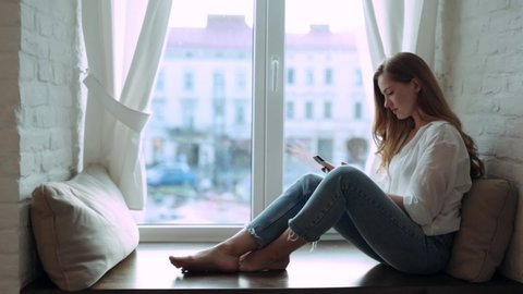 At home young woman sitting on a windowsill use phone communication female looking message cellphone cheerful smile use internet modern smartphone portrait slow motion