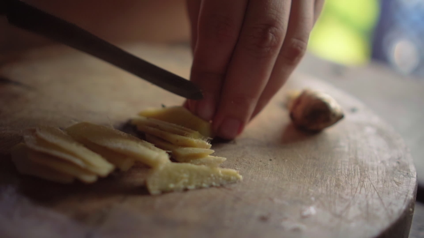 Lady chopping ginger to pieces on wooden board. Slow motion. | Shutterstock HD Video #1036345082