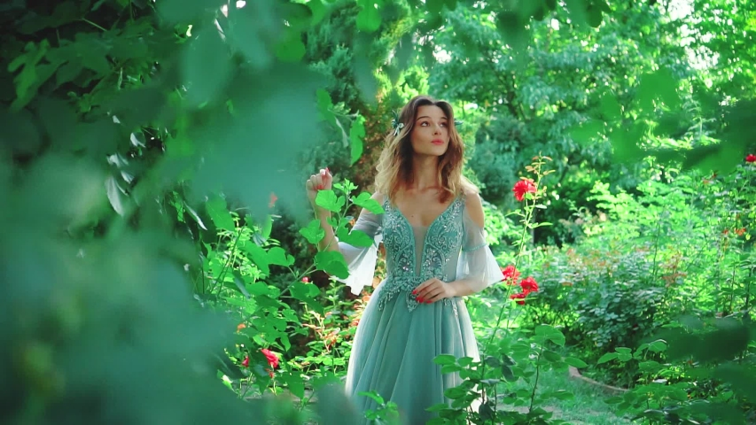 A woman in a luxurious evening dress of turquoise color walks in the garden among blooming roses. Princess with stylish styling on her loose hair. Fashionable image of a graduate girl at a prom party   Shutterstock HD Video #1036491002