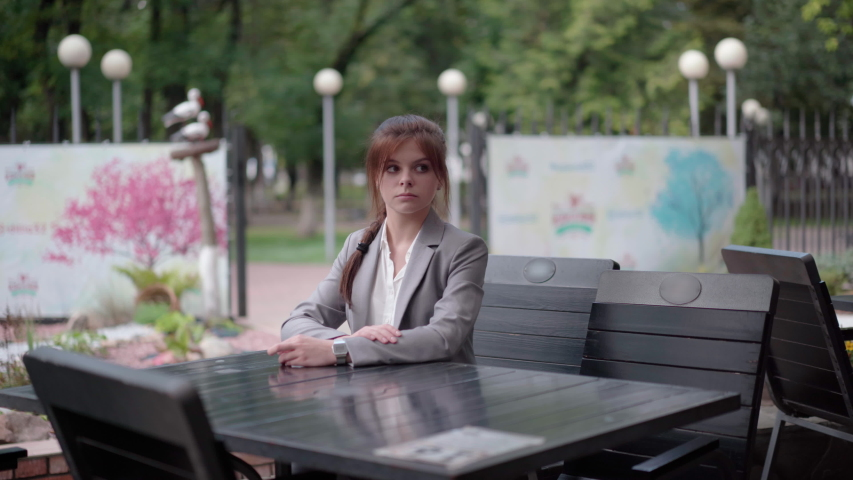 A young girl in a street cafe is waiting for a waiter. | Shutterstock HD Video #1036669202