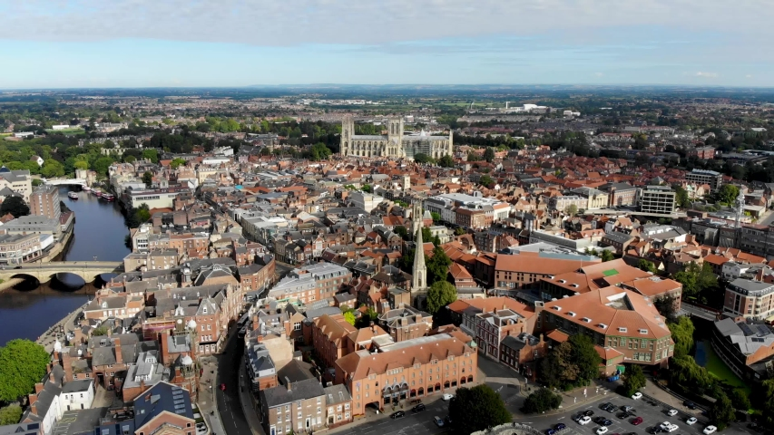 Aerial footage of the town of York located in North East England and founded by the ancient Romans, the footage shows the York Minster Historical Cathedral in the main town centre along the river. | Shutterstock HD Video #1036686482