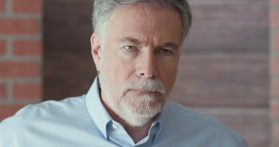 Portrait of an attractive middle aged bearded Caucasian man deep in thought who goes from looking off camera to staring solemnly into it. | Shutterstock HD Video #1036889852