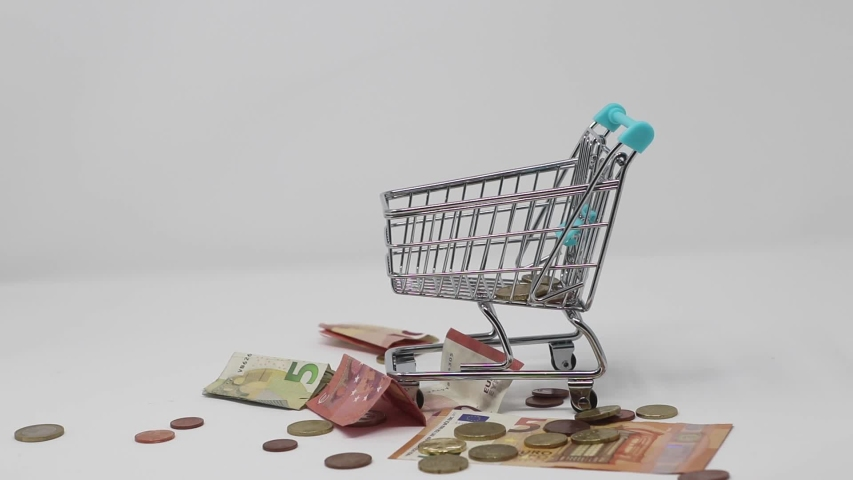 Shopping cart with a rain of coins and banknotes | Shutterstock HD Video #1036908212