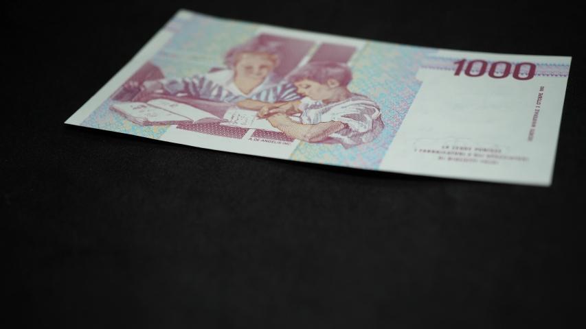 Man hand rests on black table Italian Lira banknotes of go amounts | Shutterstock HD Video #1036965632