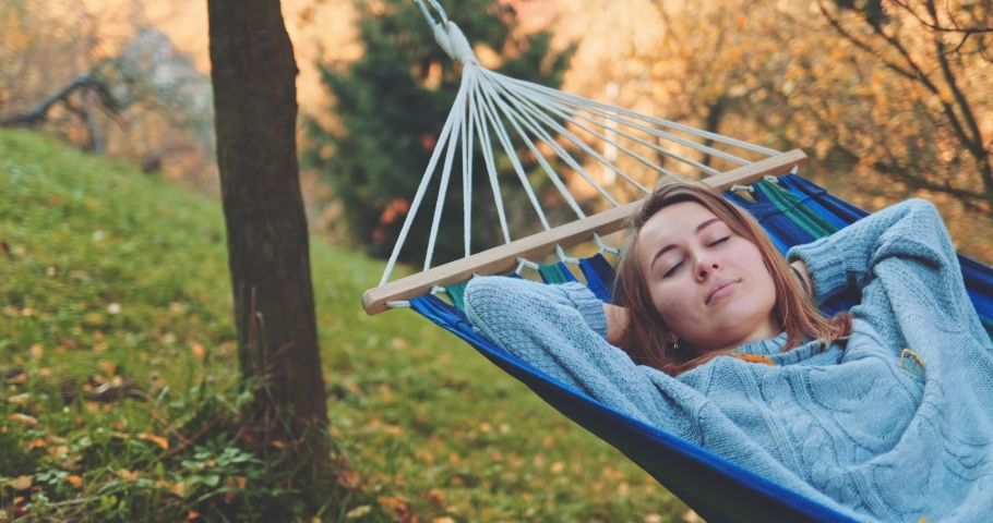 Woman Relaxes in a Hammock in Autumn. SLOW MOTION. Young woman daydreams, unwinds in a calm fall outdoor, rural country nature with colourful forest in background. Cozy morning or evening. | Shutterstock HD Video #1037024642