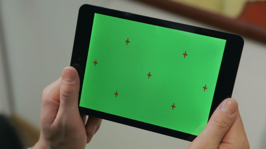Man holding in hands tablet pc with chroma key screen. Man using tablet with green screen for internet surfing online. Close up chromakey screen with marker | Shutterstock HD Video #1037048612