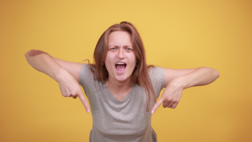 Brunette girl in gray t-shirt over isolated orange background shows emotions | Shutterstock HD Video #1037057882