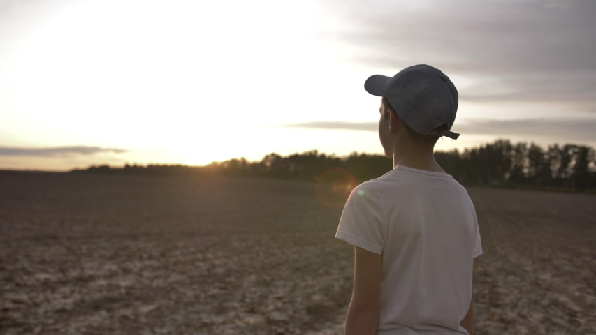 Boy raised hands to the sky and looks at the sun, outdoors at sunset | Shutterstock HD Video #1037175482